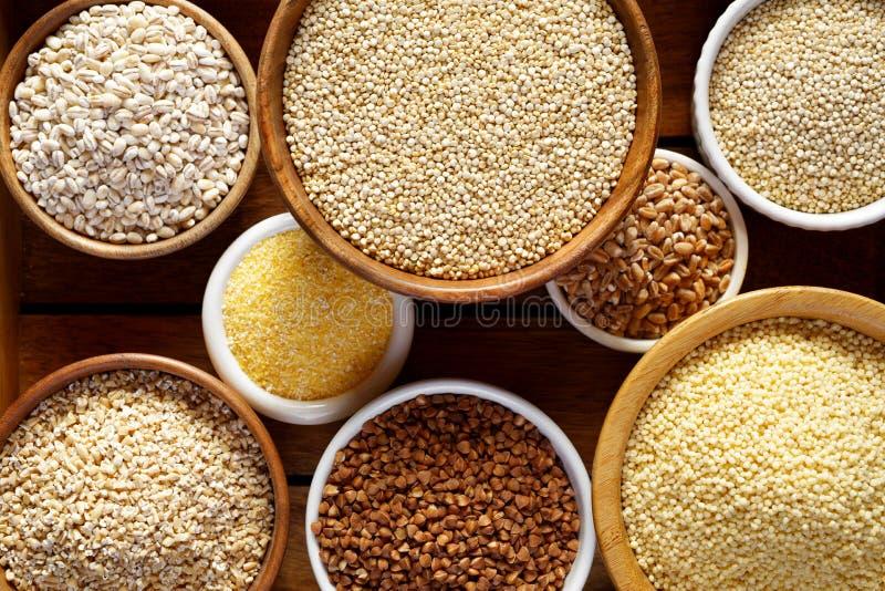 各种各样的少量,谷物 少量的不同的类型在碗的在木背景,顶视图,关闭 免版税库存图片