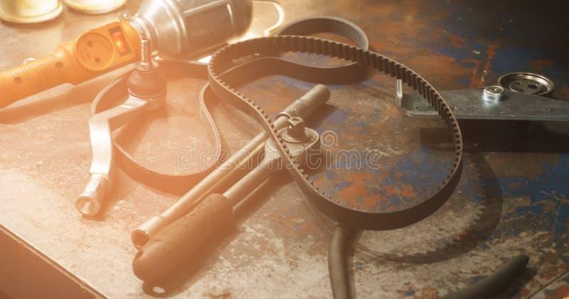 各种各样的工具和备件在一张肮脏的生锈的桌上在一个自动车间 免版税库存图片