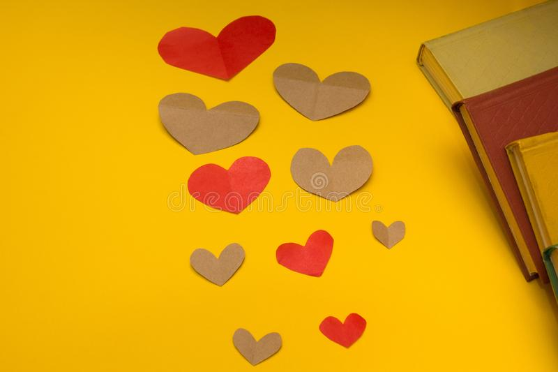 各种各样的心脏和书在黄色背景 库存照片