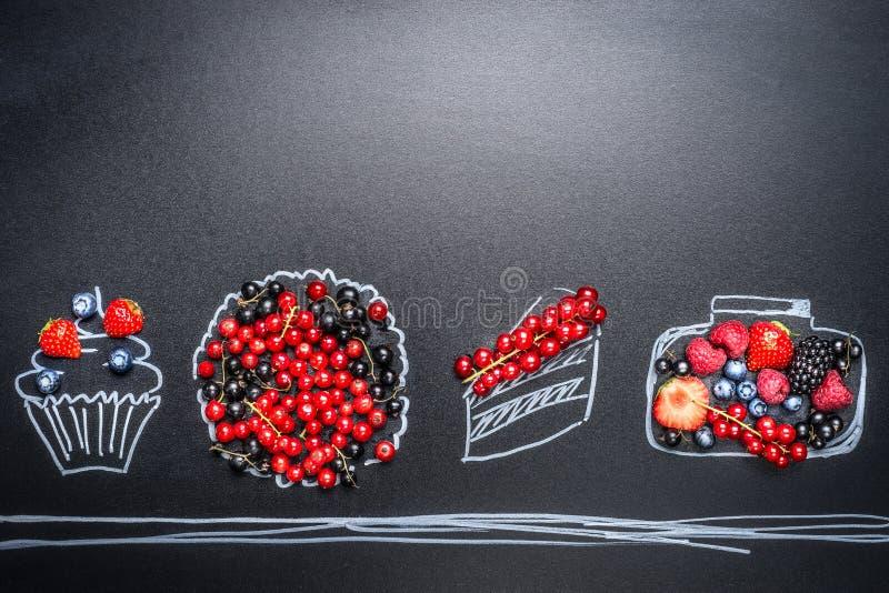 各种各样的新鲜的夏天莓果和被绘的杯形蛋糕、蛋糕、馅饼和果酱瓶子在黑板背景 免版税库存照片