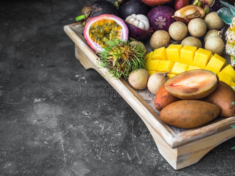 各种各样的新鲜的泰国果子-红毛丹,芒果,山竹果树,龙眼,果实,西番莲果,salak,在一个木盘子和灰色 库存照片