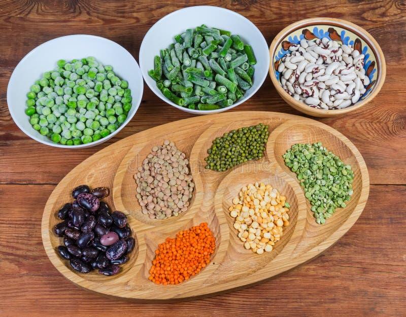 各种各样的未煮过的干和冷冻豆类用不同的盘 库存照片