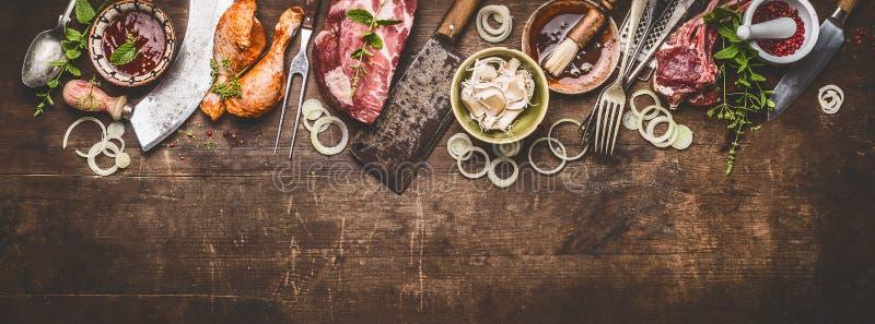 各种各样的格栅在土气木背景的bbq肉与年迈的厨房和屠户工具 免版税库存图片