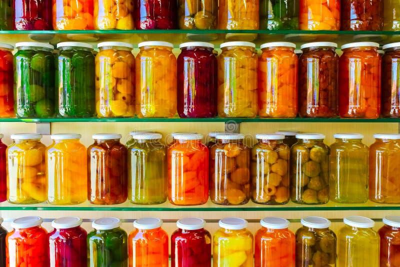 各种各样的瓶子用家装于罐中的水果和蔬菜在玻璃架子阻塞 免版税图库摄影