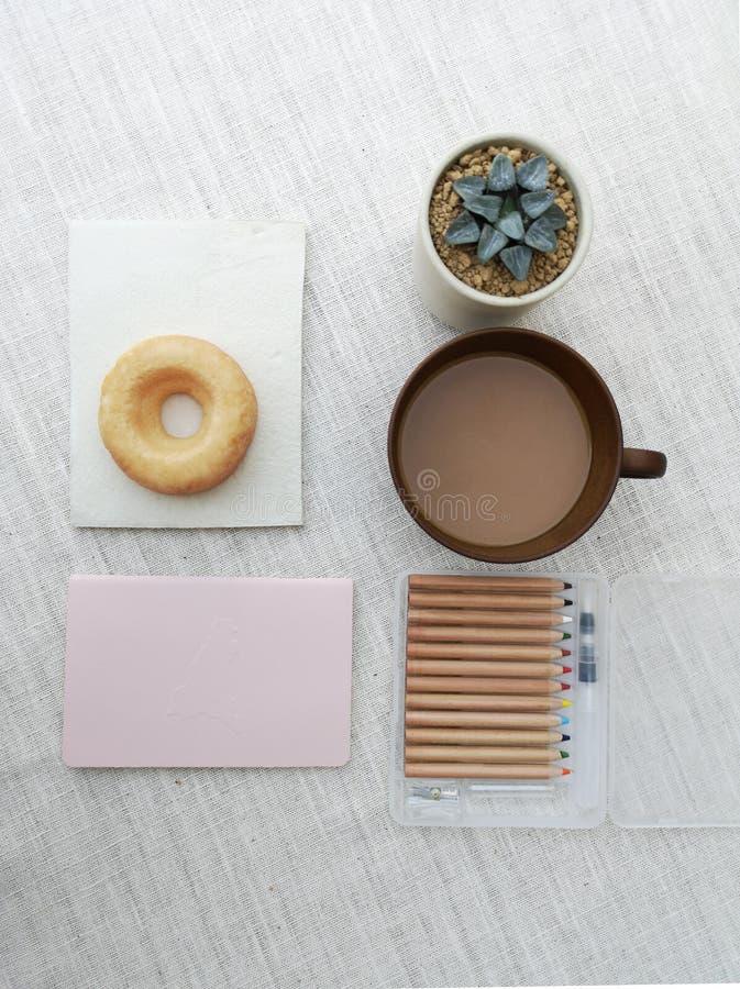 各种各样的盆的仙人掌房子植物的汇集,与一杯咖啡的多福饼,图画材料,为速写的得心应手的工具,顶面 免版税库存图片