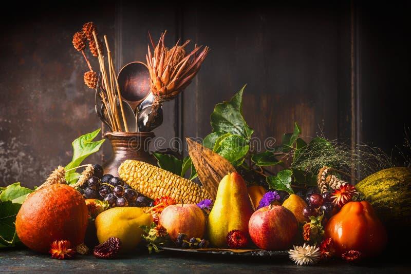 各种各样的秋天水果和蔬菜在黑暗的土气厨房用桌上在木背景,侧视图 免版税库存图片