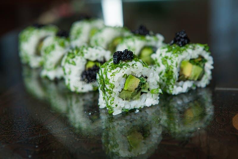各种各样的种类寿司食物在黑背景服务 关闭与鱼和米的鲜美新寿司卷在板材 卷射击工作室寿司 免版税库存照片