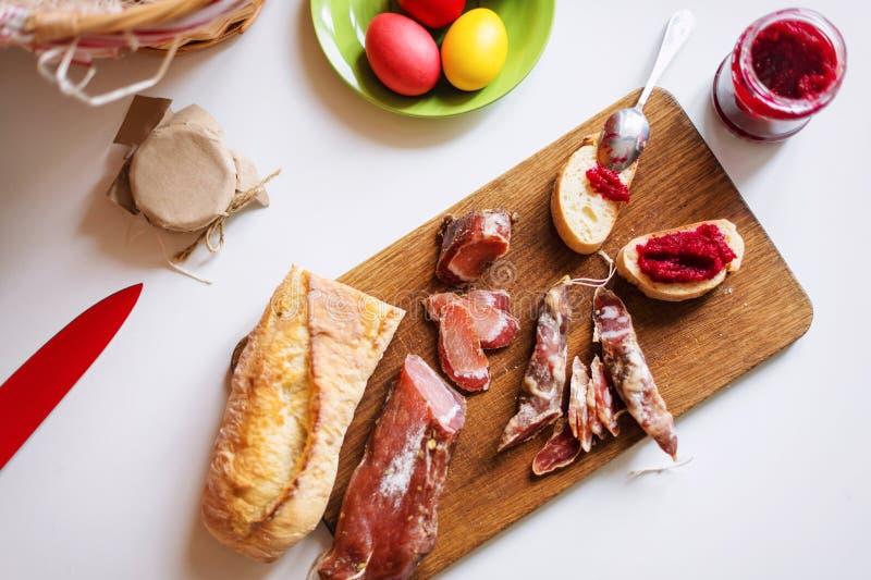 各种各样的肉的顶视图水平的图象在服务板的 火腿、猪肉、牛肉、复活节彩蛋和家制面包用甜菜根horsera 免版税库存图片