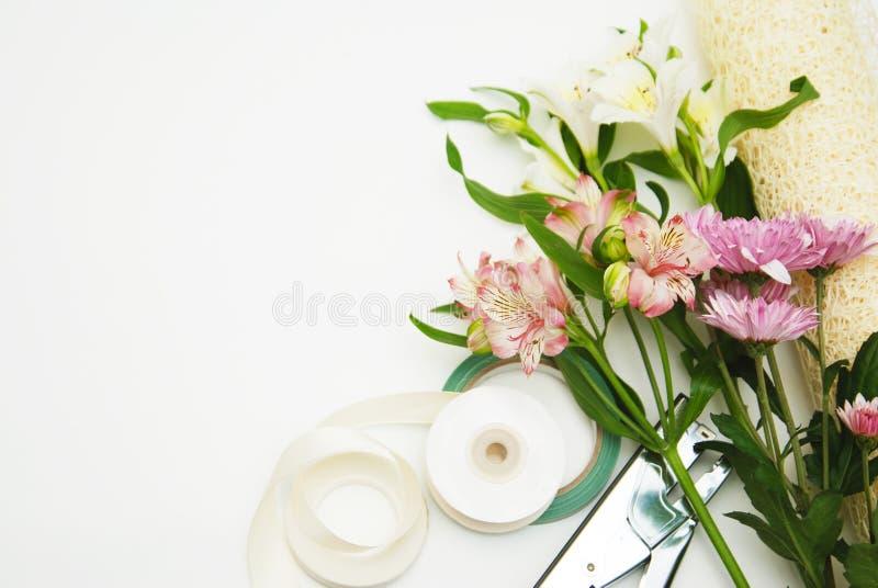 各种各样的花和庭院或卖花人工具在thecorner在温暖照亮背景,顶视图 复制空间 桃红色 免版税库存照片