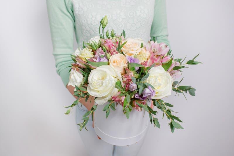 各种各样的花混杂的花束在一个帽子箱子的在woman& x27; s手 免版税库存图片