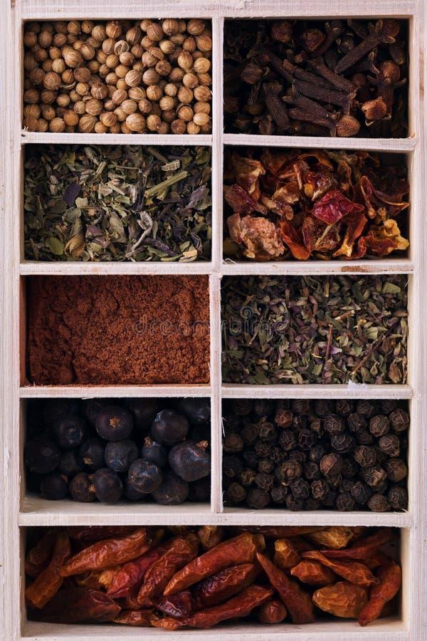 各种各样的草本和粉末香料在一个木箱 库存照片