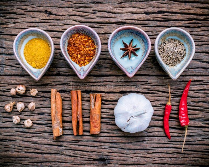各种各样的草本和香料在陶瓷碗 食物和烹调ingr 免版税库存图片
