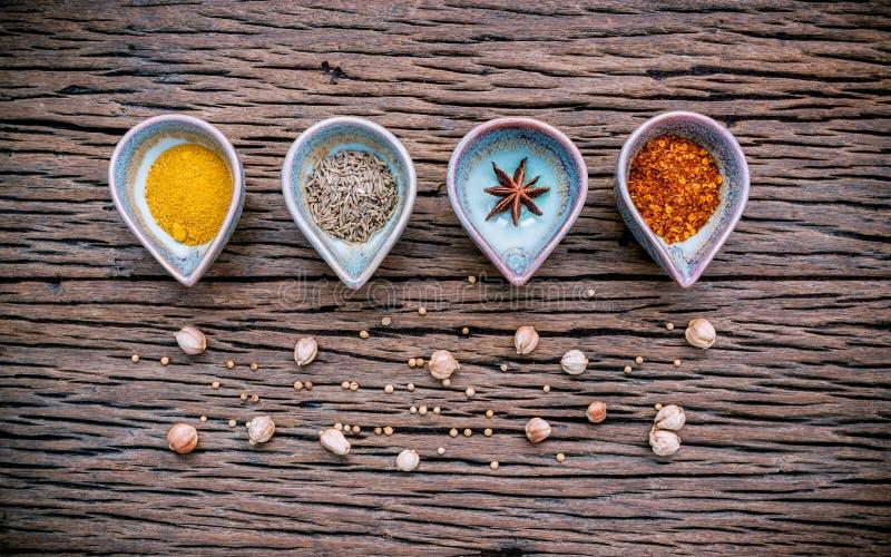 各种各样的草本和香料在陶瓷碗 食物和烹调ingr 免版税库存照片