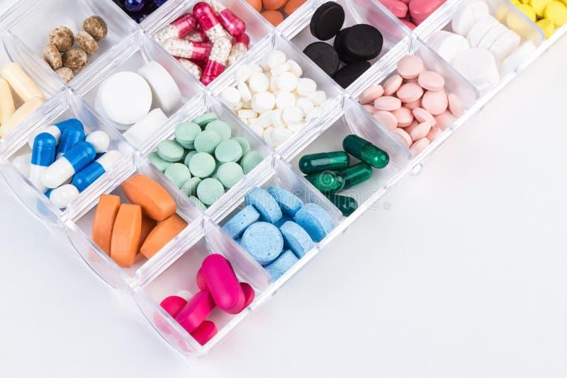 各种各样的药片和胶囊在塑胶容器 免版税库存图片