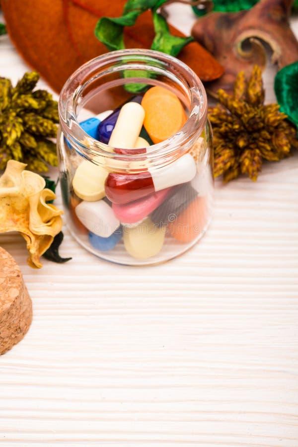 各种各样的药片和胶囊在玻璃容器有绿色的 库存照片
