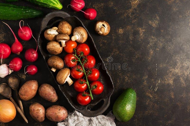 各种各样的菜和蘑菇在土气陶器 概念吃健康 黑褐色背景,顶视图,拷贝温泉 免版税库存照片
