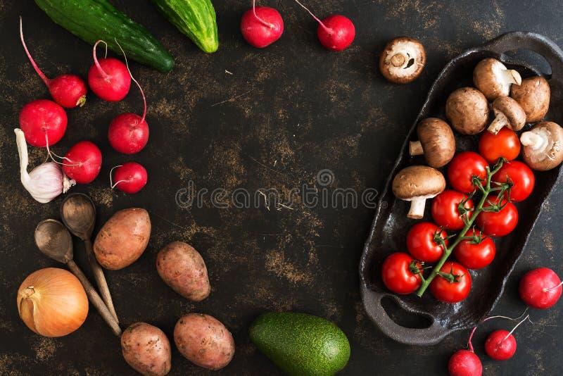 各种各样的菜和蘑菇在土气陶器 黑褐色背景,顶视图,文本空的中心 免版税库存照片