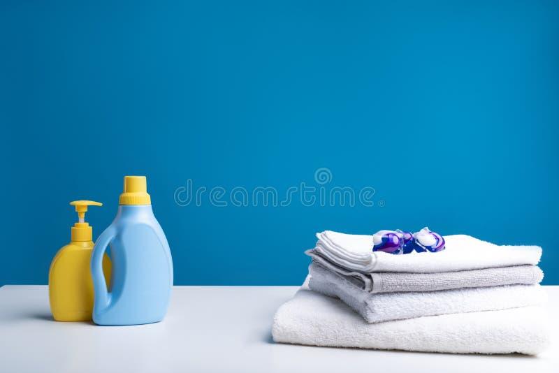 各种各样的说谎在桌上的洗涤剂和干净的洗衣店 免版税库存照片