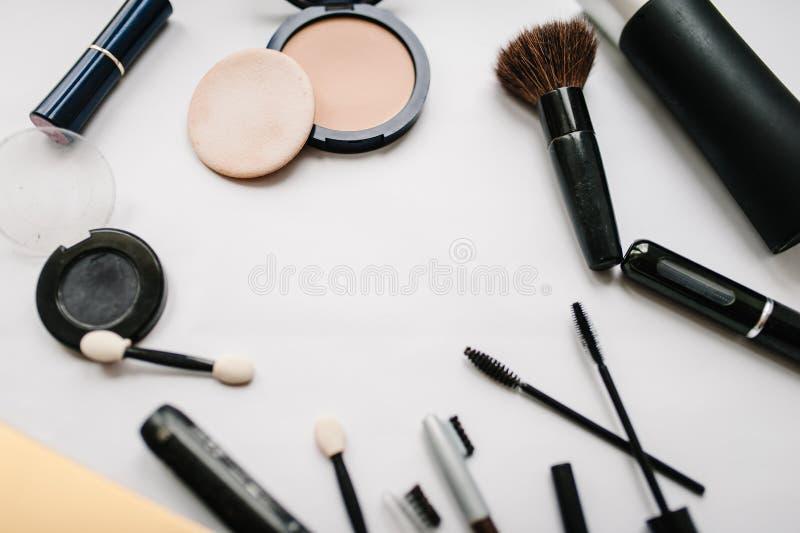 各种各样的集合构成产品:刷子,眼影膏,粉末,染睫毛油,在轻的白色背景隔绝的化妆用品 库存图片