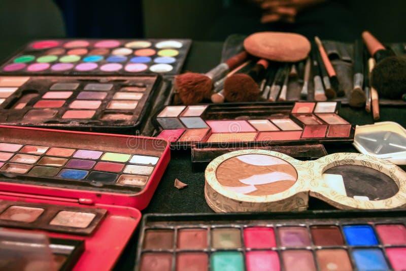 各种各样的颜色化妆用品,那在用于对要从appropr引人注意的顾客的构成的桌被安置 免版税库存照片