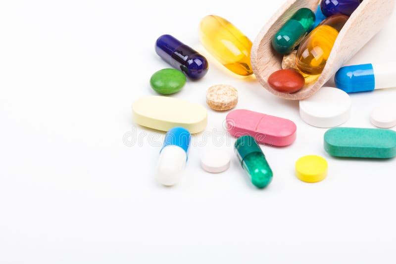 各种各样的颜色药片和胶囊与木dispencer 免版税库存图片