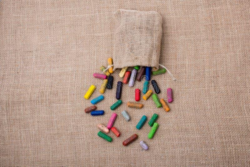 各种各样的颜色蜡笔在大袋外面的 库存照片