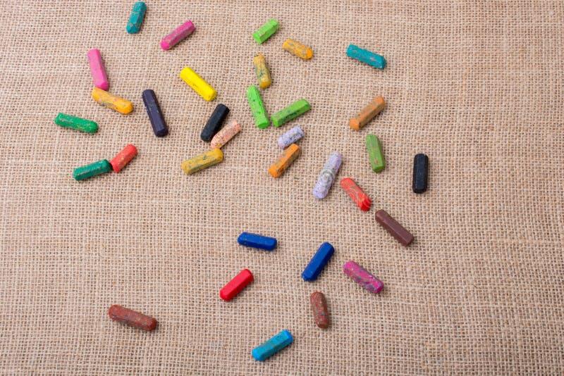 各种各样的颜色蜡笔在帆布的 免版税库存图片