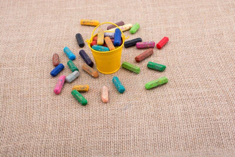 各种各样的颜色蜡笔在桶的 库存图片