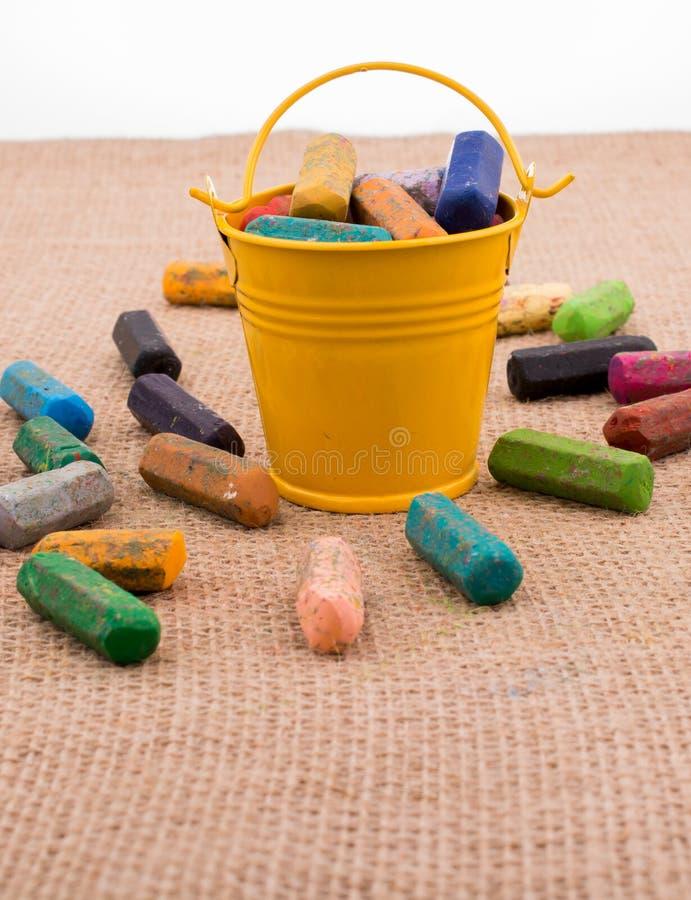 各种各样的颜色蜡笔在桶的 免版税库存图片