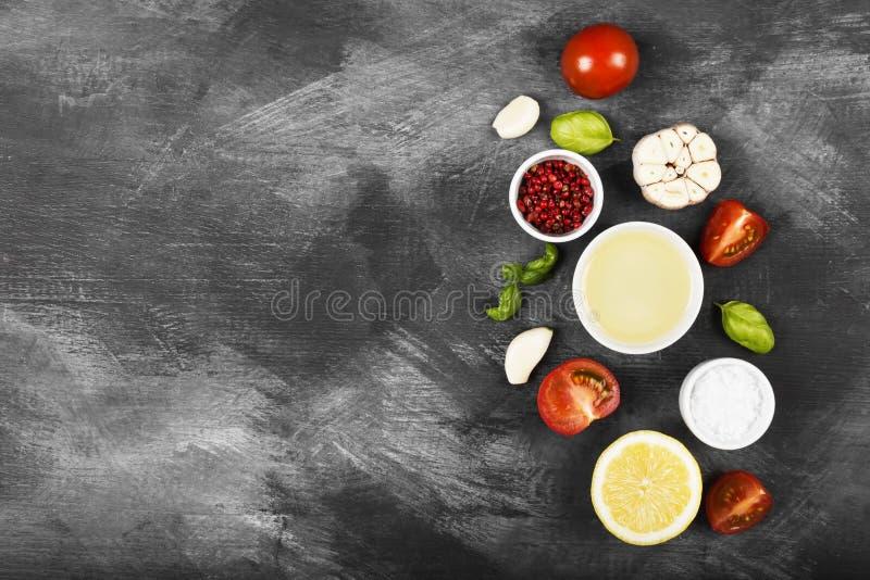各种各样的香料、草本和菜在黑暗的背景 库存图片