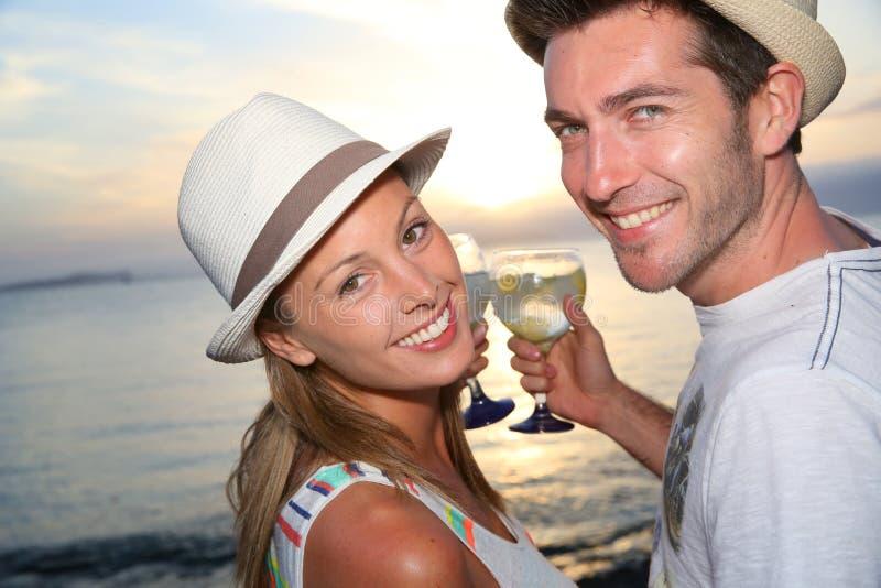 结合享受鸡尾酒时间在海滩的日落 库存图片