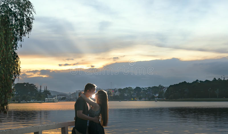 他结合亲吻在日落下来对湖岸  库存照片