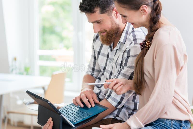 合作与他的女性工友的快乐的年轻人 免版税库存图片
