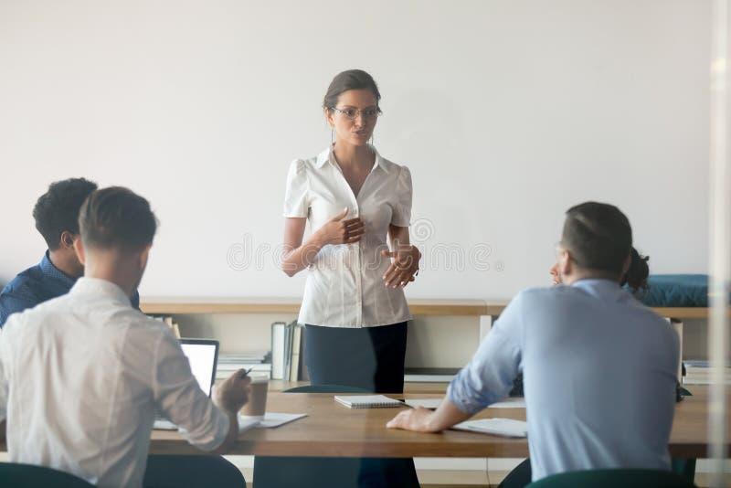合作与雇员的严肃的女性报告人谈话在见面 免版税图库摄影
