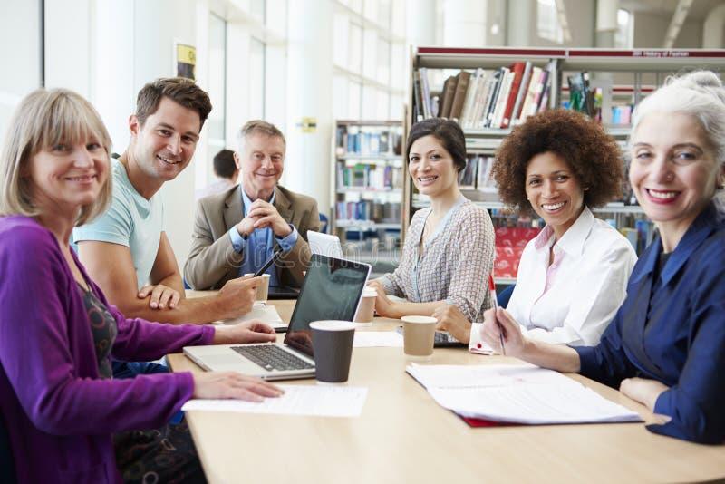 合作在项目的小组成熟学生在图书馆里 免版税库存照片