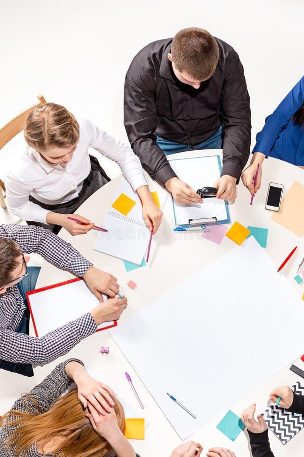 合作坐在书桌后,检查报告,谈话 顶视图 库存照片