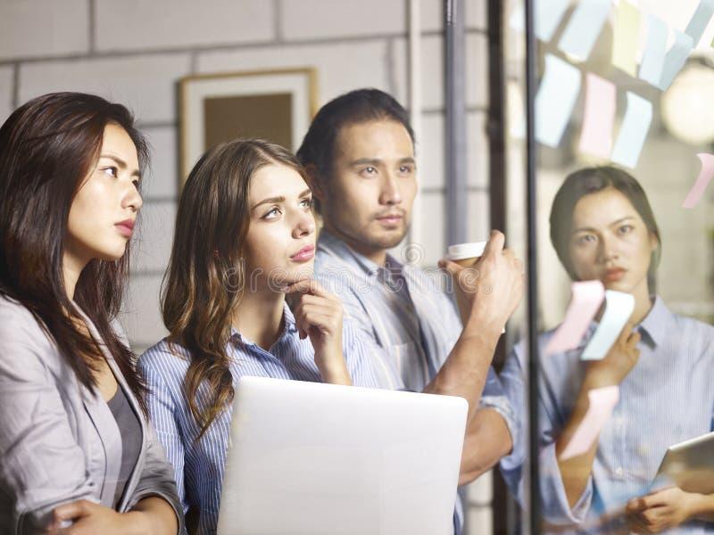 合作见面在办公室的亚裔和白种人企业家 库存照片