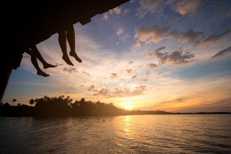 结合剪影和观看的太阳在海滩的日落在泰国 免版税库存照片