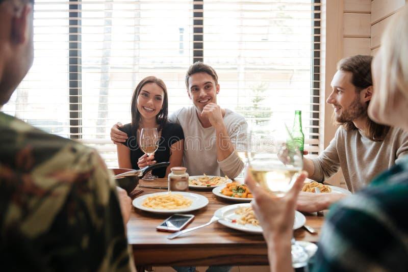 结合吃晚餐和谈话与厨房的朋友 图库摄影