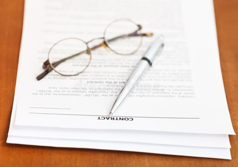 合同和银笔和镜片在桌上 库存照片