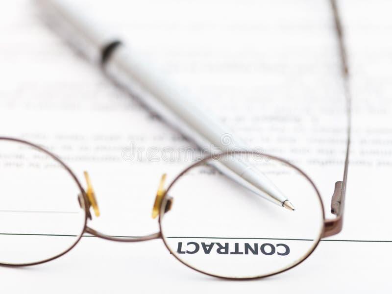 合同和银笔通过眼镜 免版税库存图片