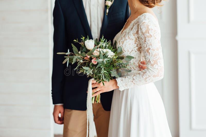 结合在一起使婚礼花束的新娘和新郎 免版税库存照片