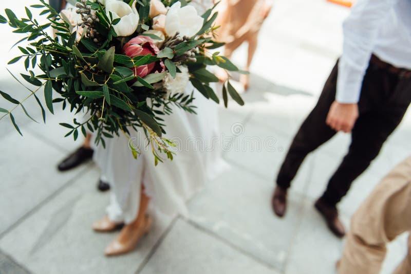 结合在一起使婚礼花束的新娘和新郎 免版税库存图片