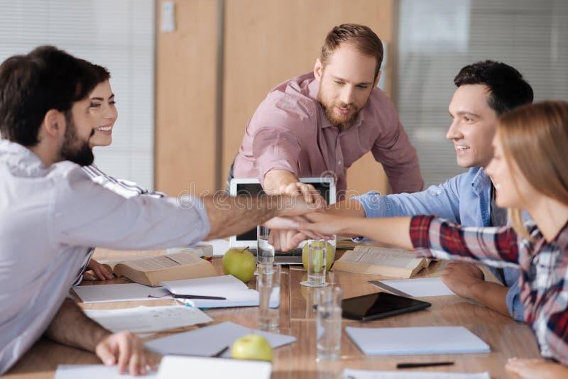 结合在一起使手的小组正面工作者在工作场所 免版税图库摄影