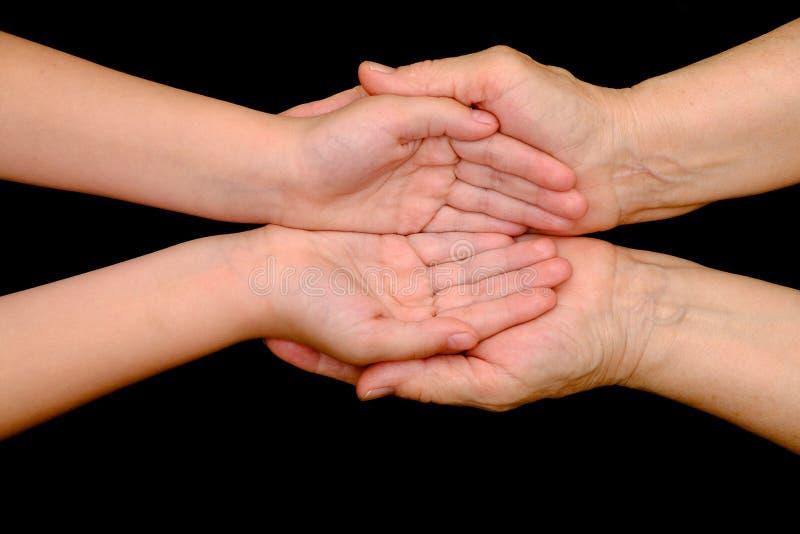 结合在一起使手的老妇人和小女孩 免版税库存照片