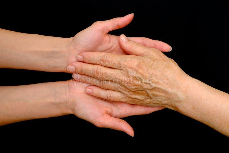 结合在一起使手的老妇人和少妇 库存图片