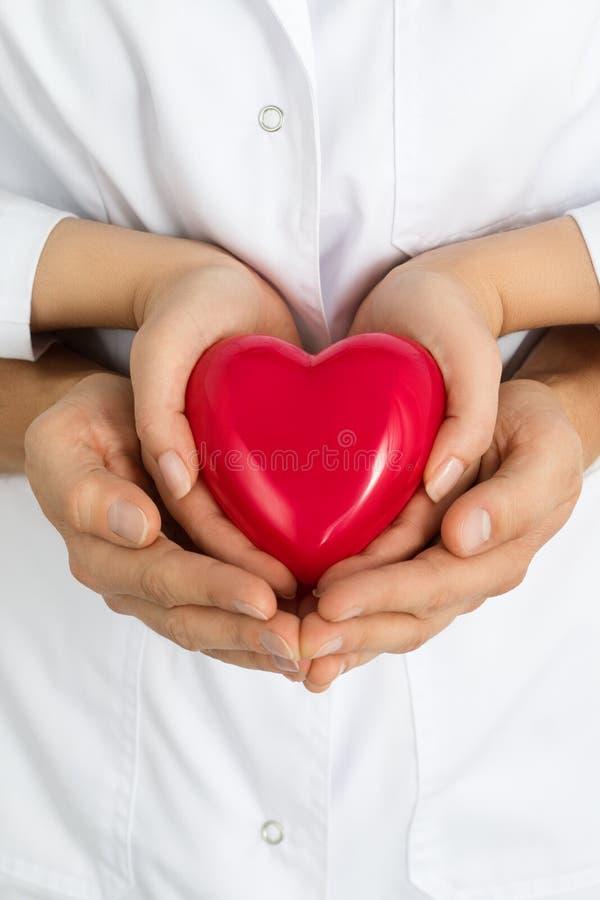 结合在一起使红色心脏的妇女的和人的手 免版税库存图片