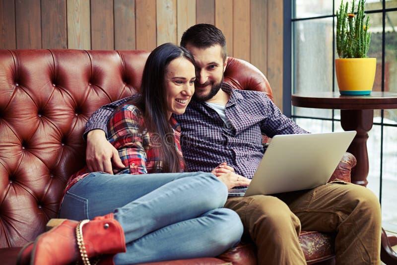 结合在家坐沙发和使用膝上型计算机 图库摄影