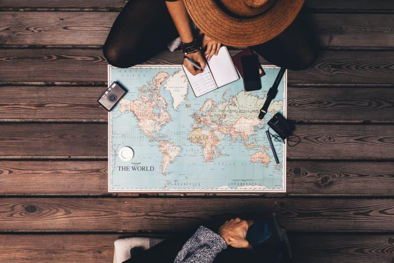结合坐由世界地图的计划假期 库存照片