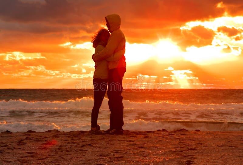 结合拥抱在爱的男人和妇女停留在与日落风景的海滩海边 免版税库存图片